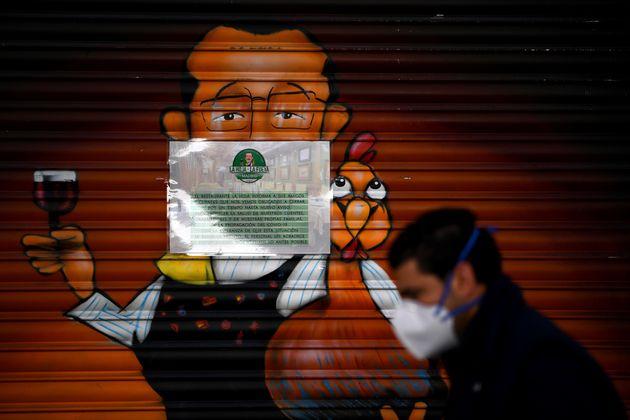 Un hombre pasa por delante de un restaurante cerrado,en