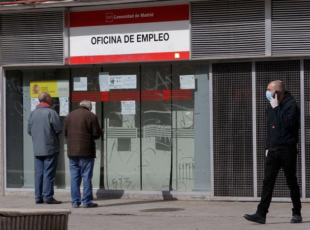 Dos personas miran la oficina de empleo tras la declaración del estado de