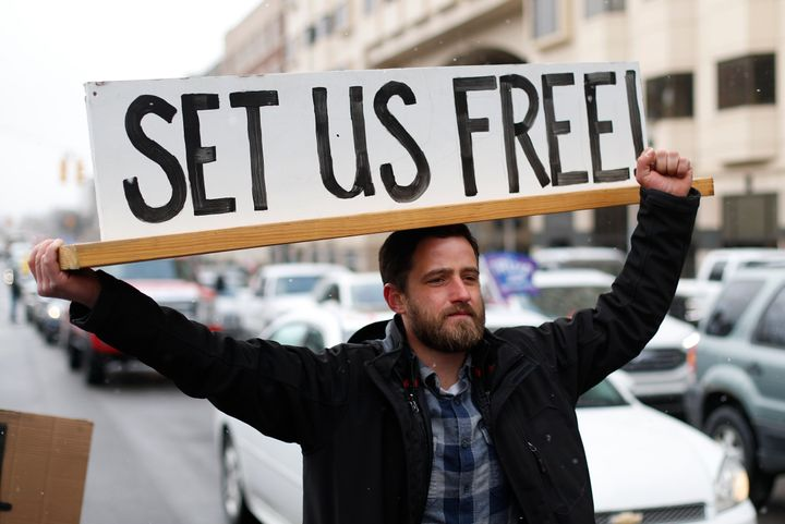 Steve Polet holds a sign during a protest at the State Capitol in Michigan last week