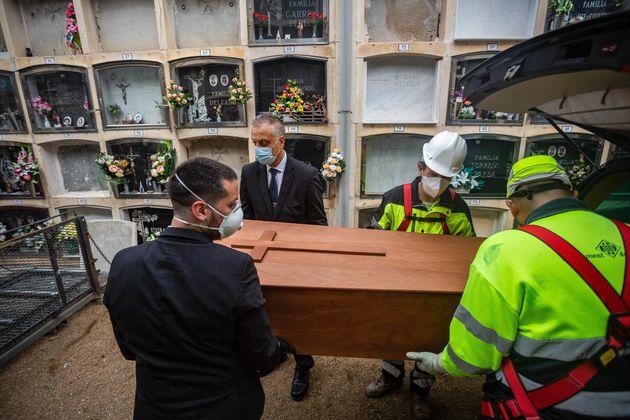 Trabajadores de una funeraria y enterradores durante un entierro en