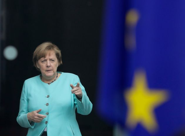 German Chancellor Angela Merkel stands behind a European flag as she waits for the arrival of Chinese...
