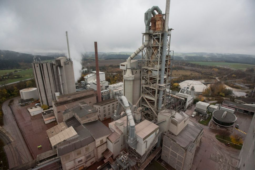 A cement kiln preheater tower, right, stands above factory buildings and storage silos at Holcim cement plant in Dotternhause
