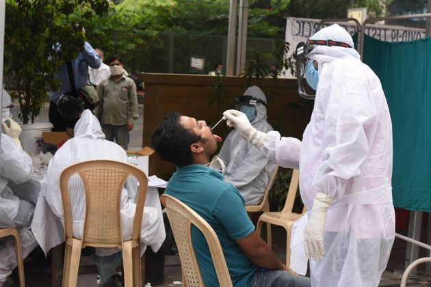 A medical worker in a PPE suit takes a swab sample while conducting a COVID-19 test for media persons,...