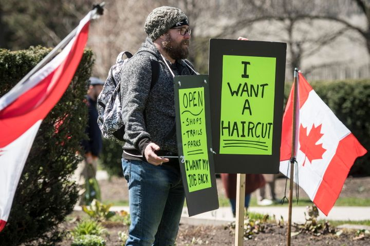 A demonstrator holds a sign during a protest to end the shutdown due to COVID-19 at Queen's Park in Toronto on Saturday.