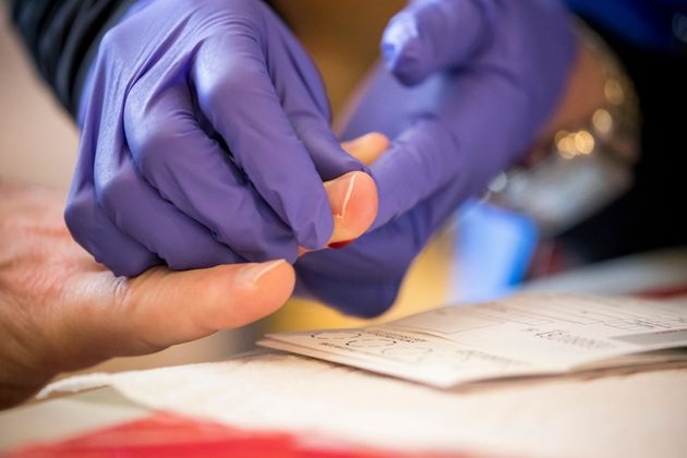 A healthcare worker takes a sample at a New York State Department of Health COVID-19 antibody testing...