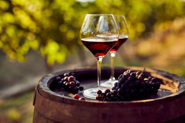 Two glasses of red wine on a wooden barrel in the