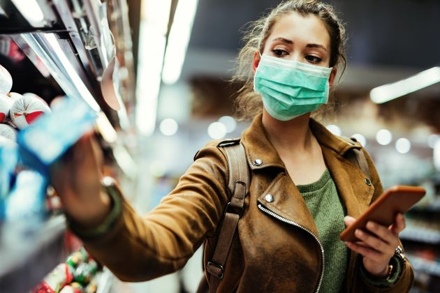 Young woman with face mask using mobile phone and buying groceries in the supermarket during virus
