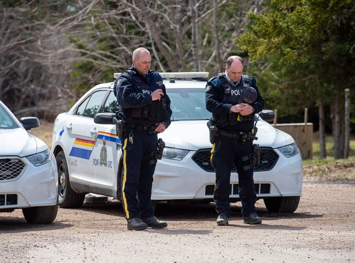 Two RCMP officers observe a moment of silence to honour slain Const. Heidi Stevenson and the other 21 victims of the mass killings at a checkpoint on Portapique Road in Portapique, N.S. on Friday.