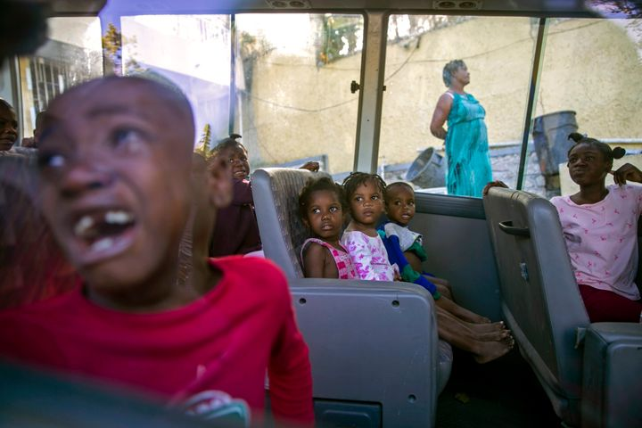 In this Feb. 14, 2020 file photo, orphans sit inside a social services bus after police removed them from a children's home r