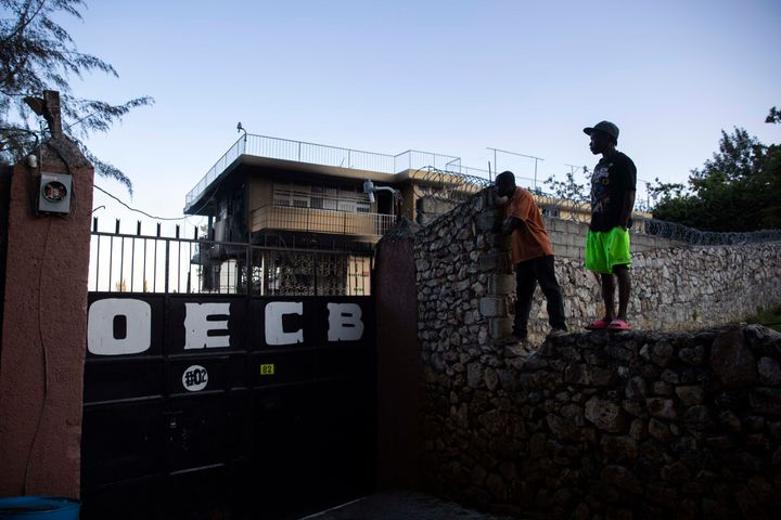 In this March 14, 2020 file photo, residents stand on top of a wall to see inside the property of a children's home run by th