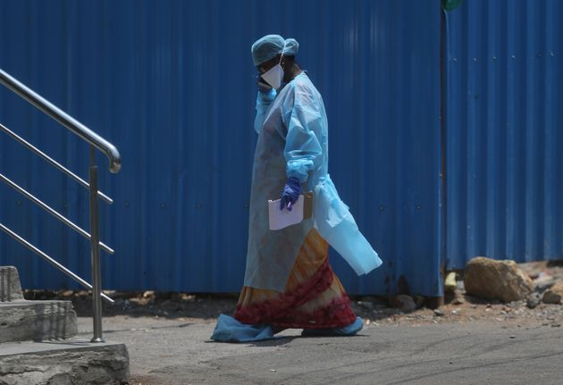 A health worker walks inside a containment zone to collect details during lockdown to prevent the spread...