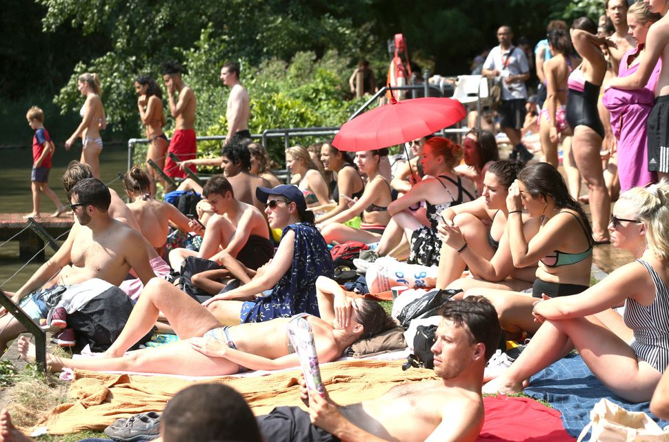 People sunbathing at the mixed bathing pond on Hampstead Heath in