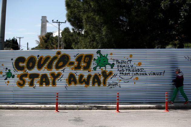 A woman walks in front of graffiti against coronavirus, written by soccer fans near the under construction...