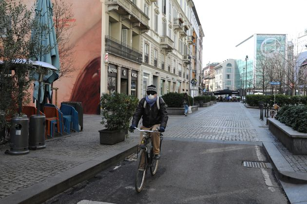 A man rides a bicycle on an empty Corso Garibaldi, a main road in the center of Milan, on February 26. Inresponse to the coronavirus pandemic, the city plans to increase bike lanes and pedestrian paths and discourage car use.