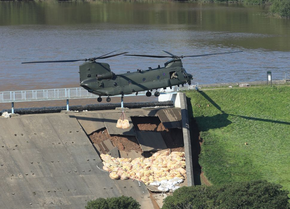 An RAF Chinook helicopter flying in sandbags to help repair the dam at Toddbrook reservoir near the village...