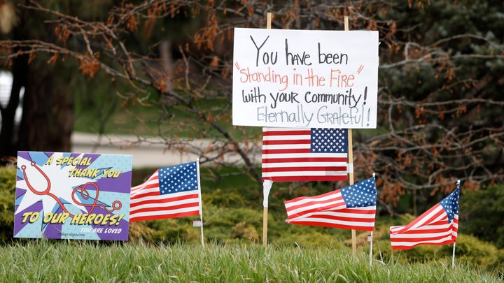 Signs and U.S. flags stand in honor of healthcare workers, across from Littleton Adventist Hospital on Sunday, April 26, 2020, in Littleton, Colo., during the coronavirus outbreak. (AP Photo/David Zalubowski)