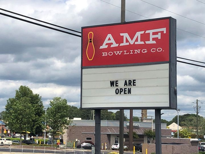 The sign outside the AMF bowling alley in Conyers, Ga., displays a message Friday, April 24, 2020, in Conyers, Ga. Like many