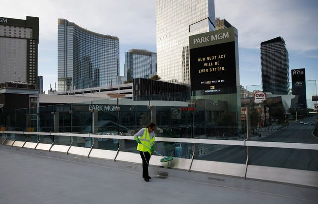 A worker cleans along the Las Vegas Strip devoid of the usual crowds as casinos and other business are...