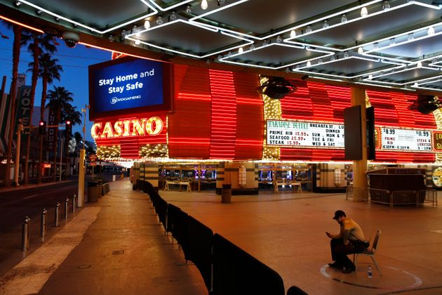 A lone security guard watches over casinos shuttered due to the coronavirus outbreak in Las Vegas, April...