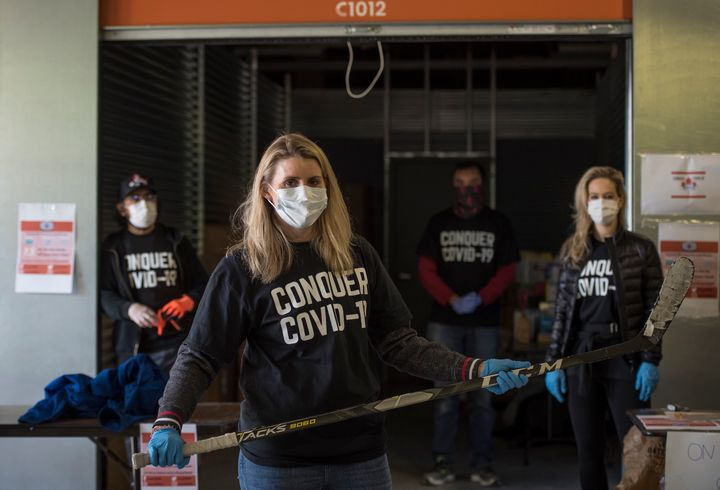 Hayley Wickenheiser poses for a photograph with volunteers during a donation drive for personal protective equipment at XYZ Storage in Toronto on April 11, 2020.