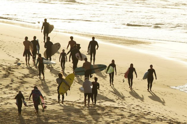 Surfers walk as Bondi Beach reopens to surfers and swimmers after it was closed to curb the spread of...