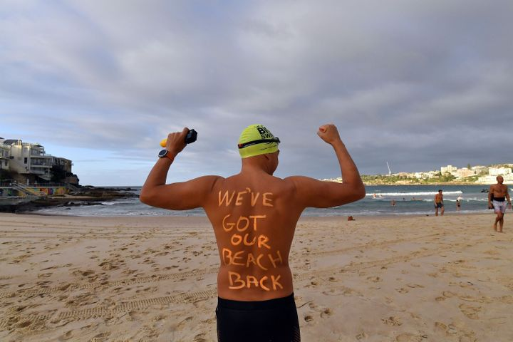 A man poses with a message on his back before enjoying his first swim after Bondi Beach reopened following a five week closure in Sydney on April 28, 2020, amid the novel coronavirus pandemic.  (Photo by SAEED KHAN/AFP via Getty Images)