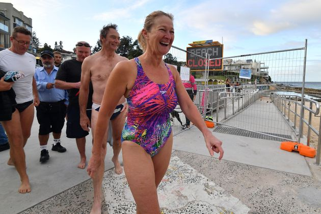 Beachgoers smile as they arrive for their first swim after Bondi Beach reopened following a five week...
