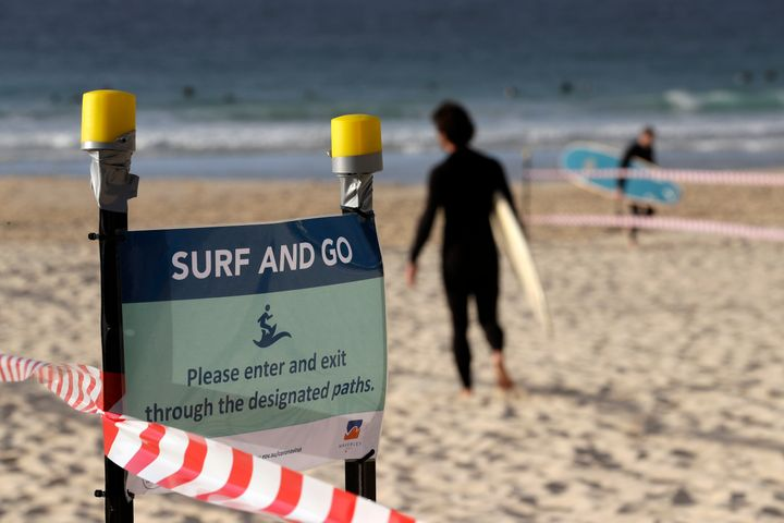 A sign tells surfers to leave once they have finished surfing at Bondi Beach in Sydney, Tuesday, April 28, 2020, as coronavirus pandemic restrictions are eased.  (AP Photo/Rick Rycroft)