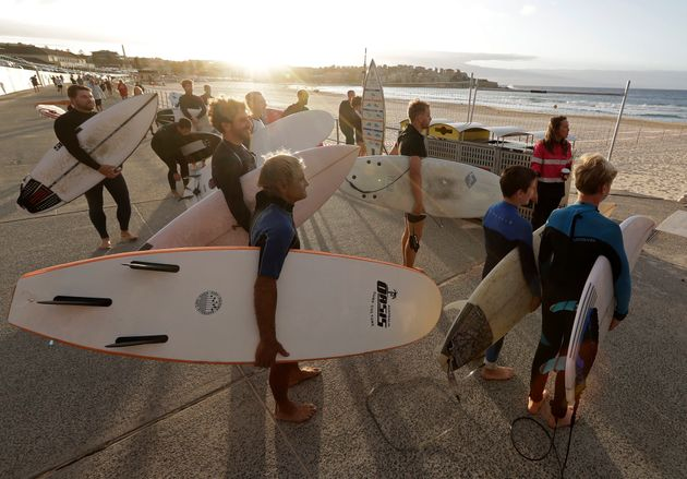Surfers wait for officials to open Bondi Beach in Sydney, Tuesday, April 28, 2020, as coranavirus pandemic...