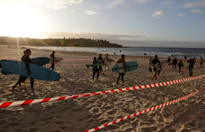 Surfers prepare to enter the water at Bondi Beach in Sydney, Tuesday, April 28, 2020, as coronavirus pandemic restrictions are eased.(AP Photo/Rick Rycroft)