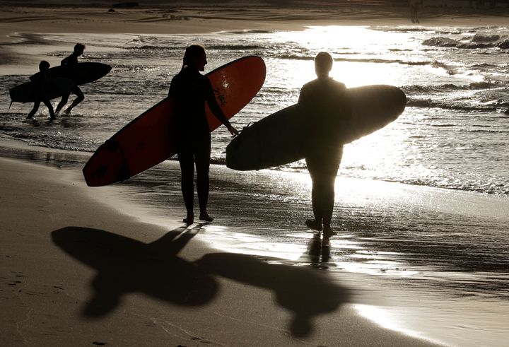Surfers prepare to enter the water at Bondi Beach in Sydney, Tuesday, April 28, 2020. (AP Photo/Rick Rycroft)