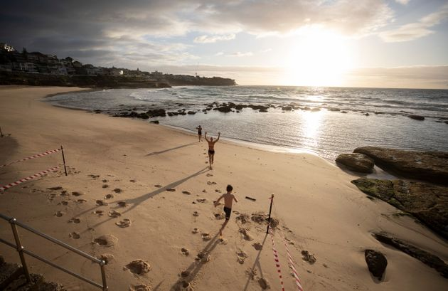 The first swimmers run into the water as Bronte Beach is reopened at Bronte Beach on April 28, 2020 in...