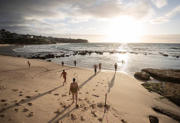 The first swimmers run into the water as Bronte Beach is reopened on April 28, 2020 in Sydney, Australia....