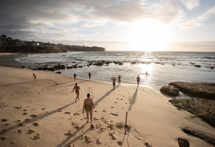 The first swimmers run into the water as Bronte Beach is reopened on April 28, 2020 in Sydney, Australia. (Photo by Ryan Pierse/Getty Images)
