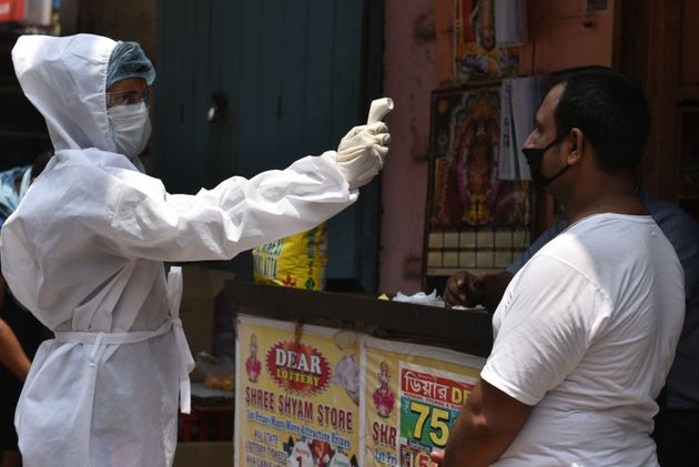 A municipal health department worker screens people for body temperature at Poddar Court area in Kolkata...