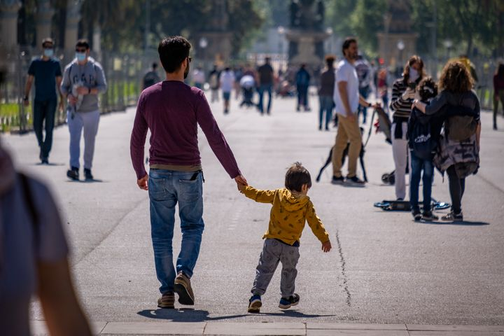 People in Barcelona, Spain, take a walk outside on April 26, the first day of allowing kids to go out for one hour with an ad