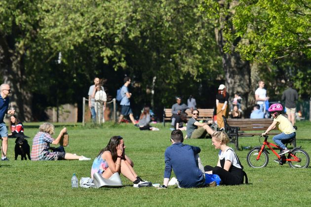 People enjoy the spring sunshine in London Fields park in east London on April