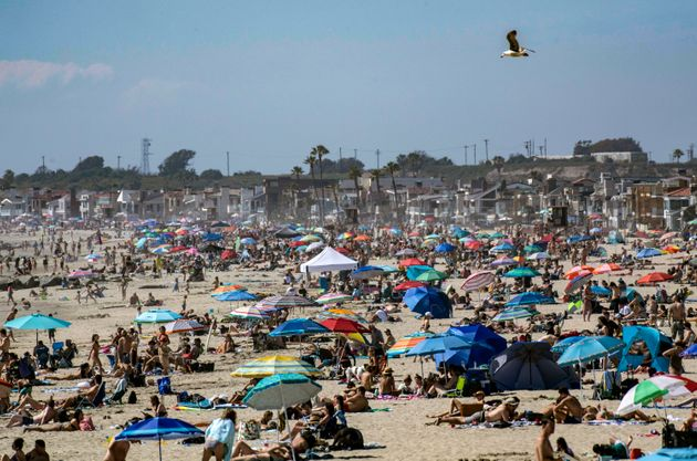 Large crowds gather near the Newport Beach Pier in California on Saturday, April 25, to cool off during...