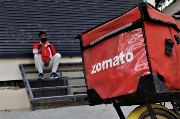 A Zomato food delivery boy takes rest near a closed shop amid COVID-19 (Coronavirus) lockdown in Gurugram...