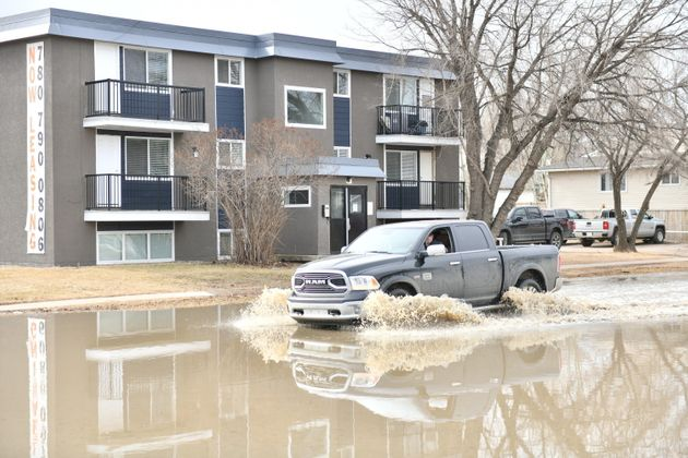 A vehicle drives through a flooded roadway Monday in Fort McMurray, Alta. Thousands of people have registered...