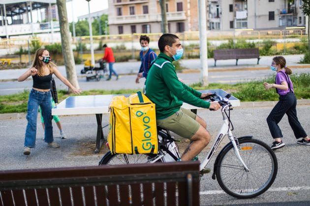 Un repartidor de Glovo circula con la bicicleta por Barcelona mientras unos niños juegan con sus