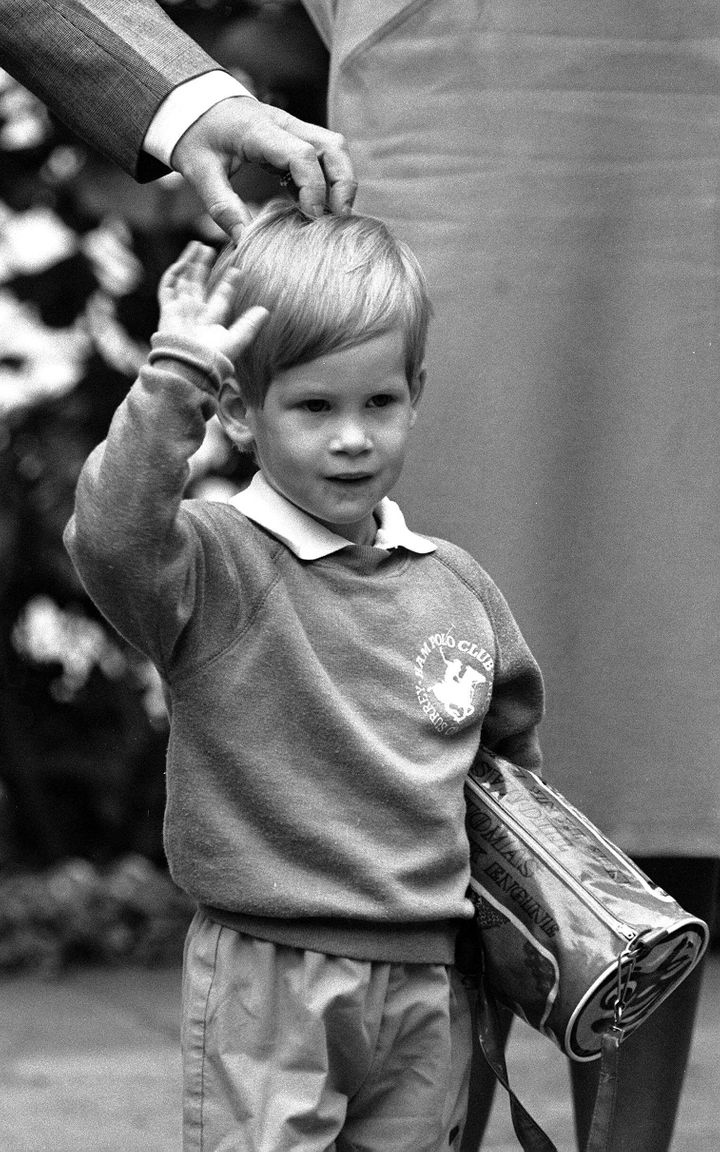 Prince Harry, then 3 years old, arrives for his first day of nursery school at Chepstow Villas in West London with a Thomas t