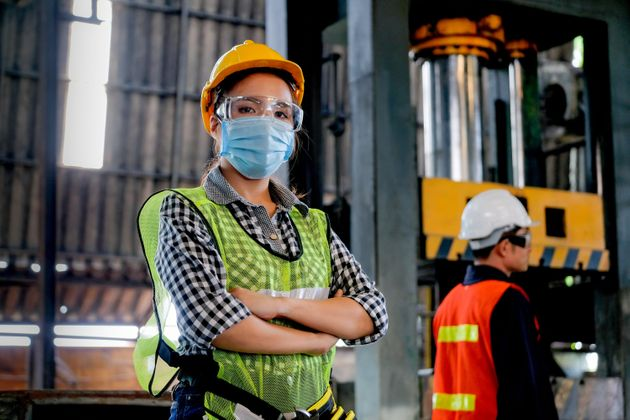Factory woman worker or technician with hygienic mask stand with confident action with her co-worker...