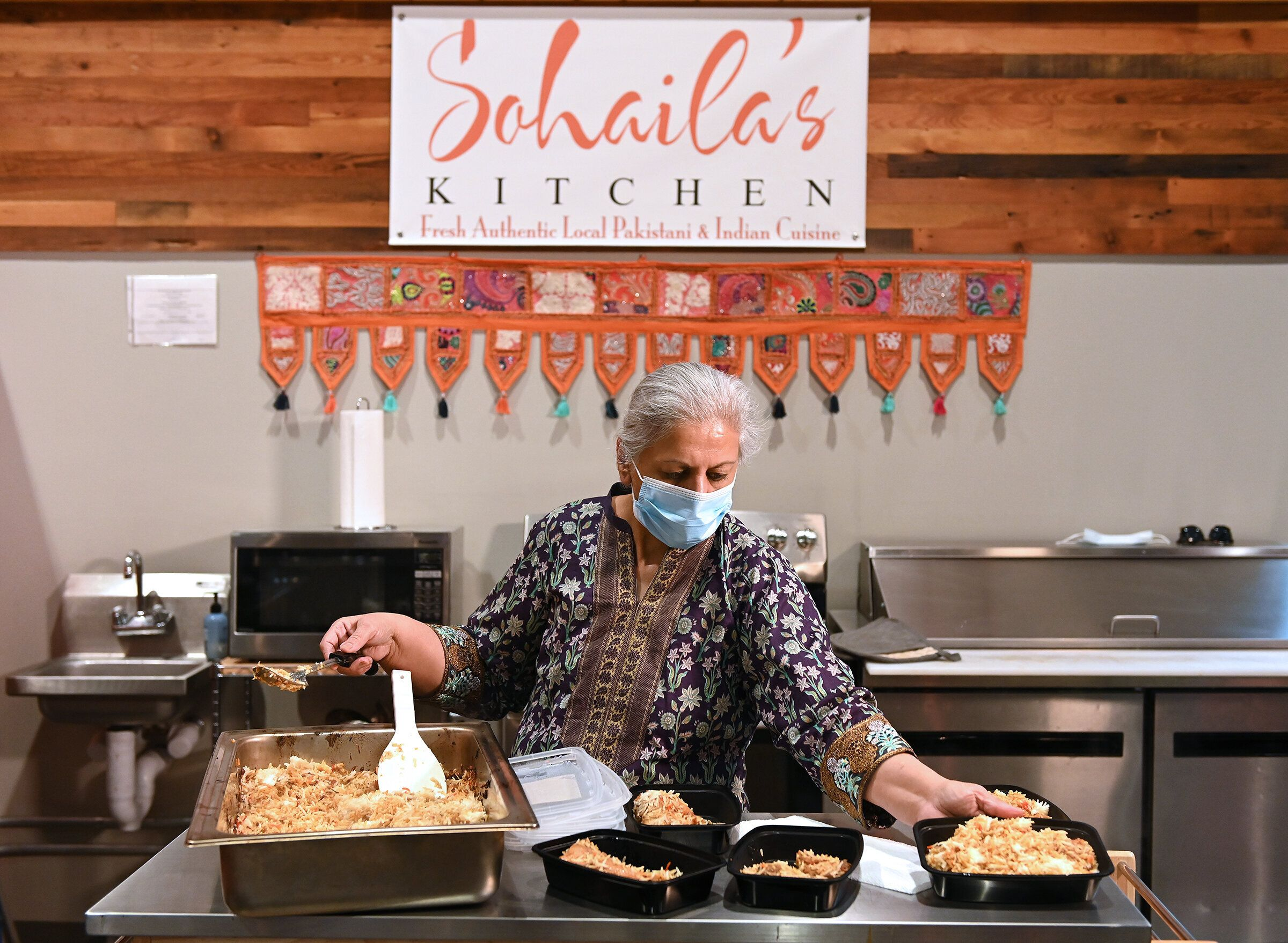 Sohaila Humayon of Sohaila's Kitchen in the Lenexa Public Market fills containers with rice for meals she is preparing for pi