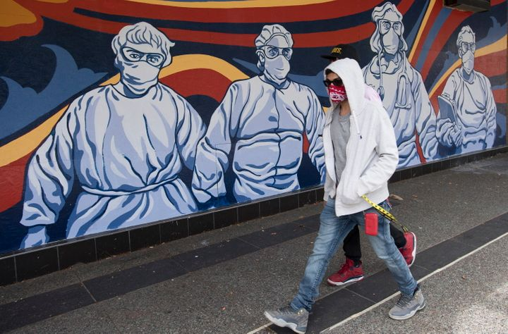 A man wearing a protective face mask walks past a mural of heath care workers painted on a boarded up restaurant in downtown