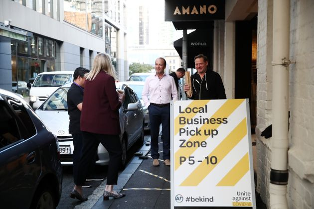 Customers wait for their coffee, bread and pastries outside Amano Bakery on April 29, 2020 in Auckland,...