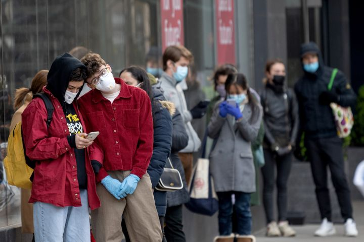 People wearing protective masks stand in line for a supermarket in New York City on April 16.