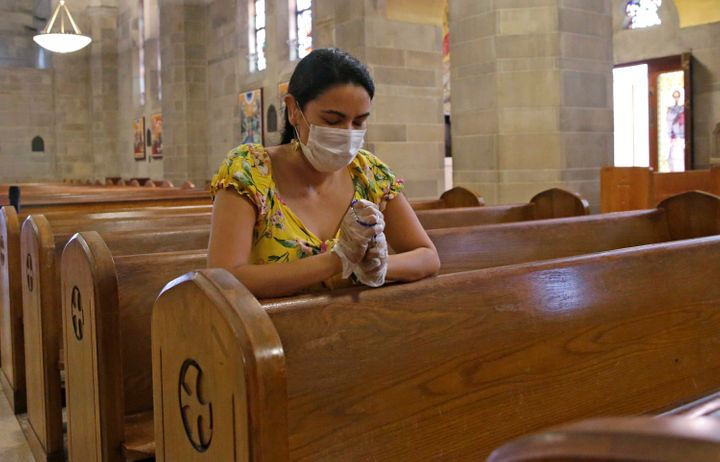 A parishioner holds a rosary while she prays wearing a mask and protective gloves at Saint Jude Melkite Greek Catholic Church