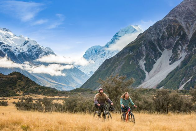 Friends ride mountain bikes through the Mount Cook National Park.