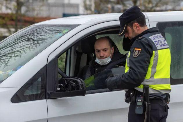 Un agente de la policía nacional para a una persona en su vehículo en un